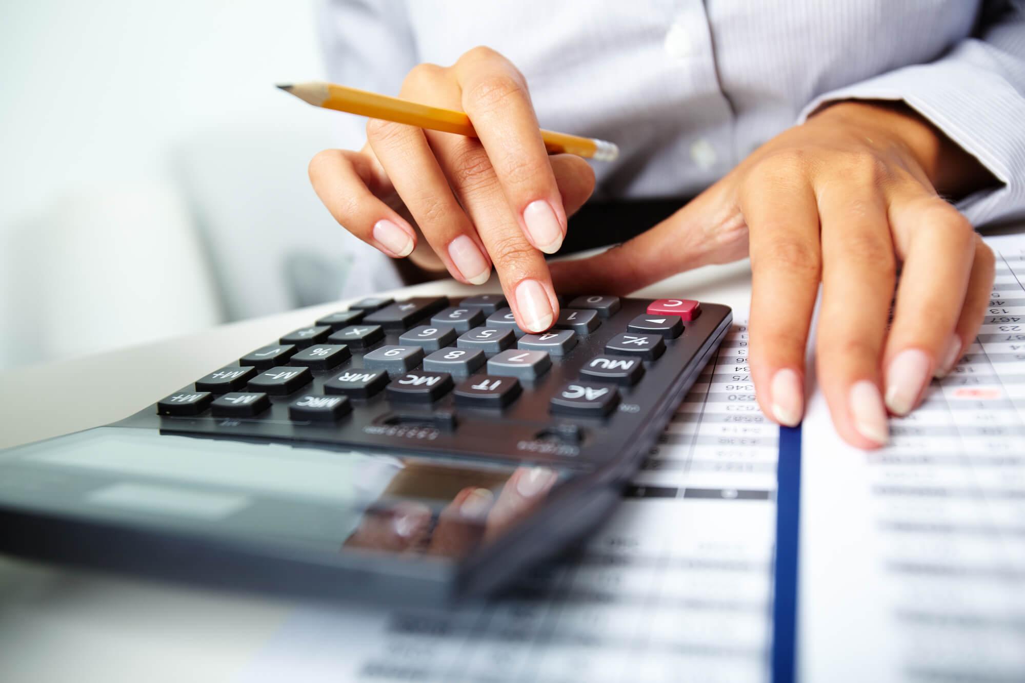 closeup of Personal Financing Strategist in West Palm Beach using a calculator