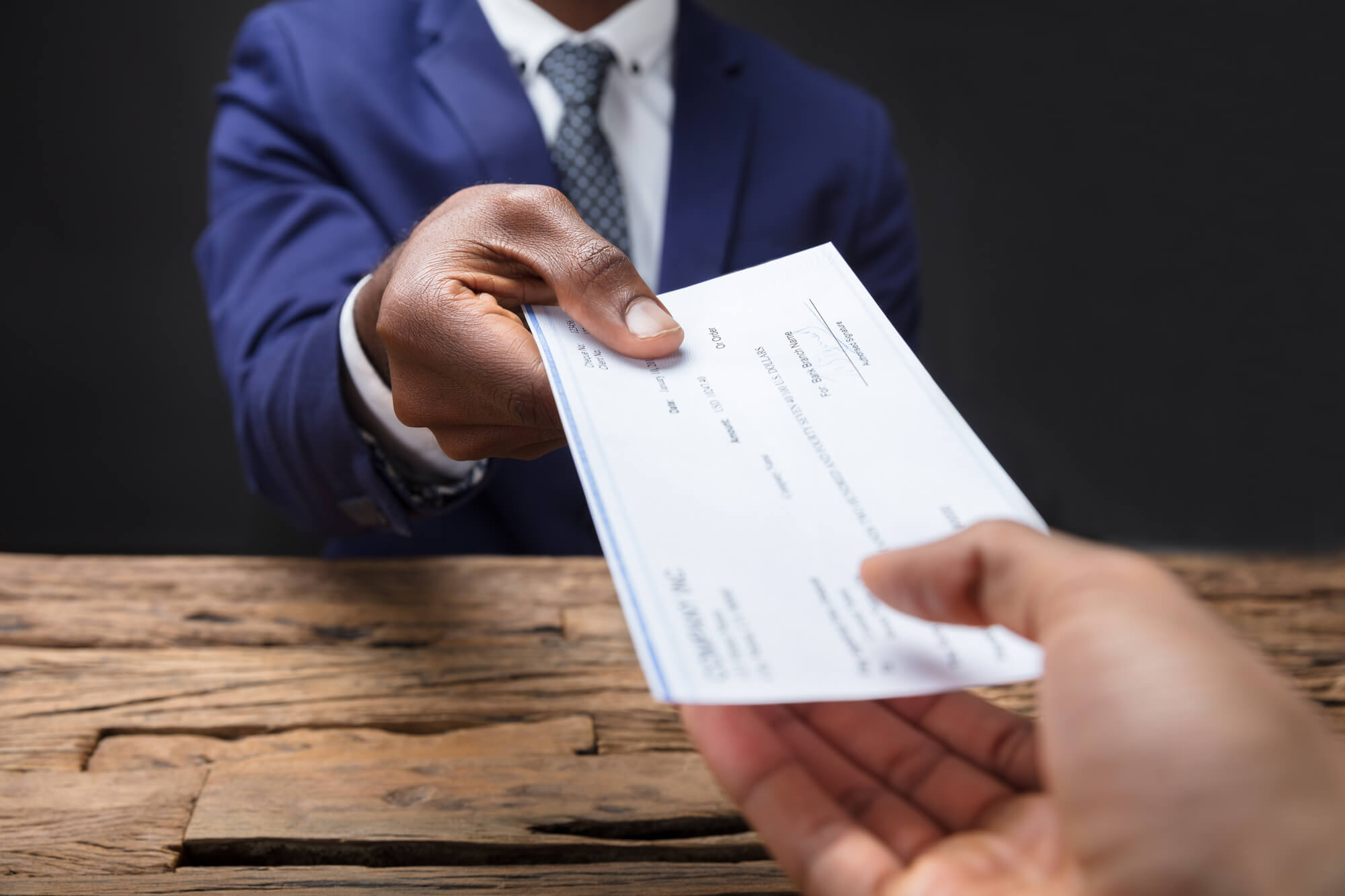 Personal Financing Strategist in West Palm Beach handing a check to someone