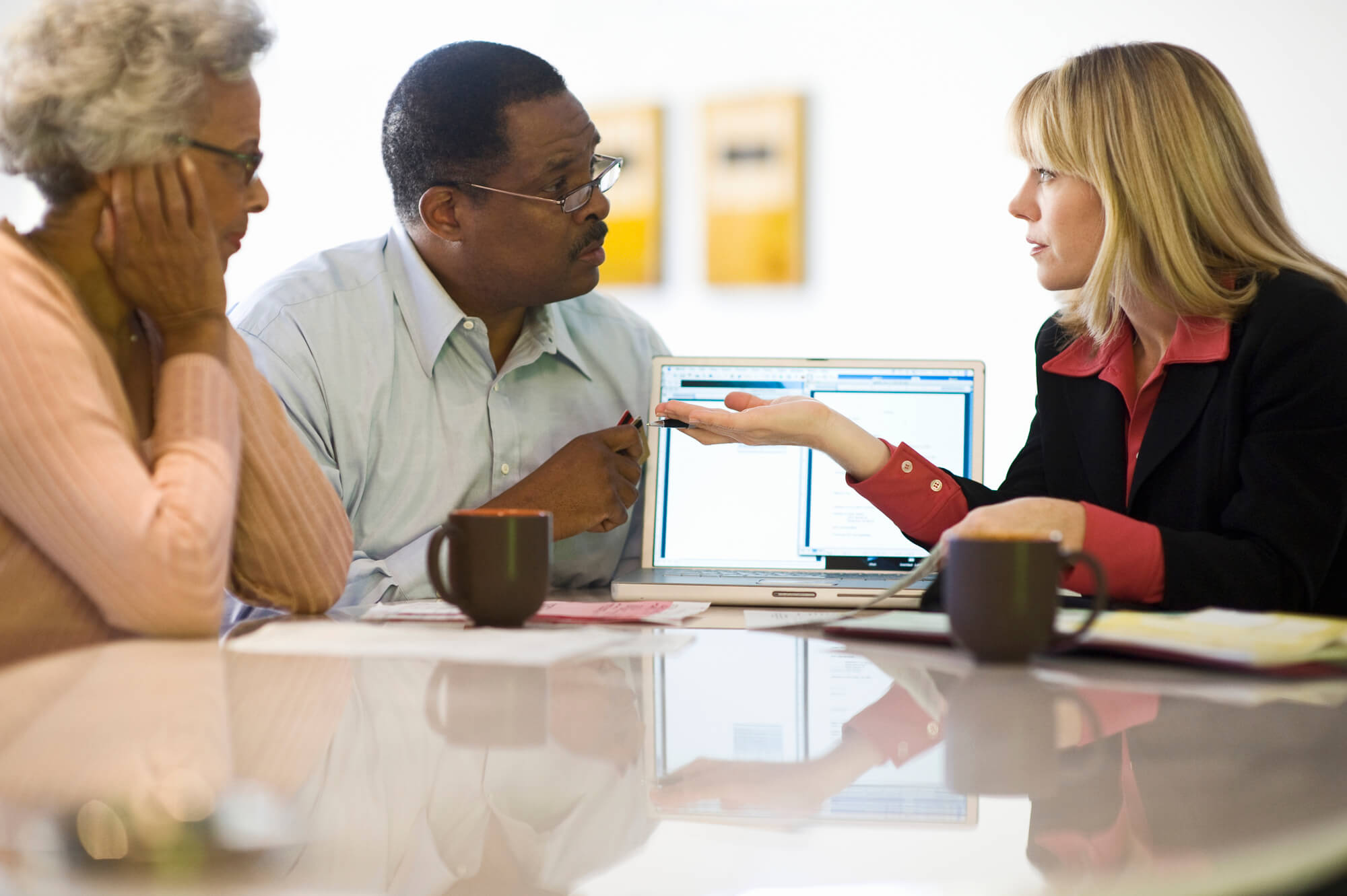 Personal Financing Strategist in West Palm Beach giving advice to an elderly couple